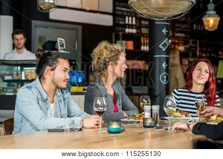 Male and female friends conversing while having food at restaurant
