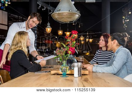 Young male waiter presenting menu to customers at table in bar