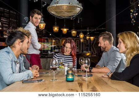 Young waiter serving food to male and female customers at table in cafe