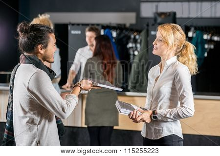 Young man giving book to female friend by bag deposit counter in cafe