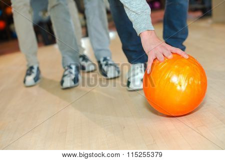 Man leaning down to pick up bowling ball