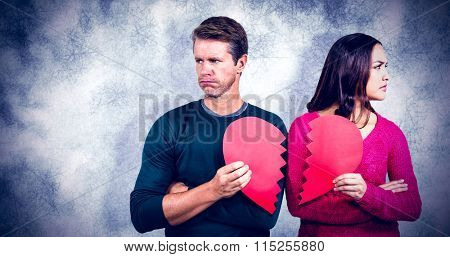 Serious couple holding cracked heart shape against grey background
