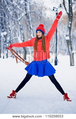 Attractive Young Woman In Wintertime Outdoor. Happy And Cheerful Girl In A Red Jacket And Blue Skirt