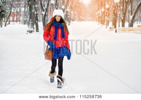 Beautiful Winter Portrait Of Young Woman In The Winter Snowy Scenery. A Girl In A White Fur Hat, A R