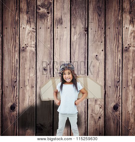 Standing girl with fake wings pretending to be pilot against wooden planks background