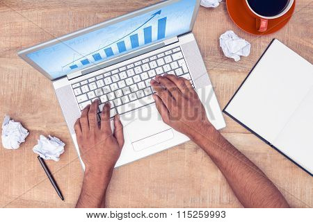 Blue data against overhead of stressed businessman using laptop