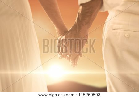 Bride and groom holding hands close up against sky and mountain
