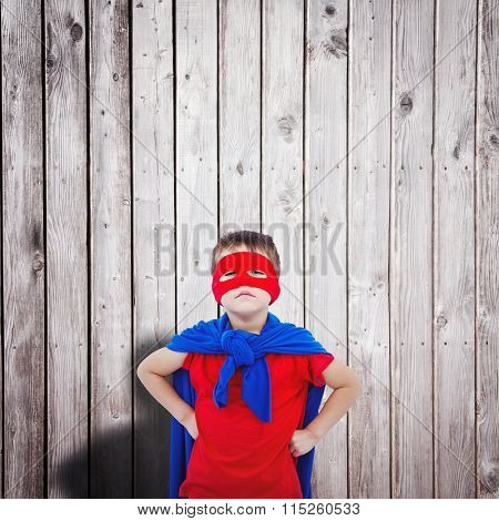 Masked boy pretending to be superhero against digitally generated grey wooden planks