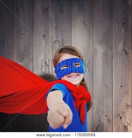 Smiling masked girl pretending to be superhero against wooden planks