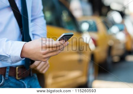 Close up male hand calling a taxi with a smartphone app. Close up of a businessman using mobile phone. Closeup detail of a businessmanâ??s hand holding a cellphone with yellow taxi in background.