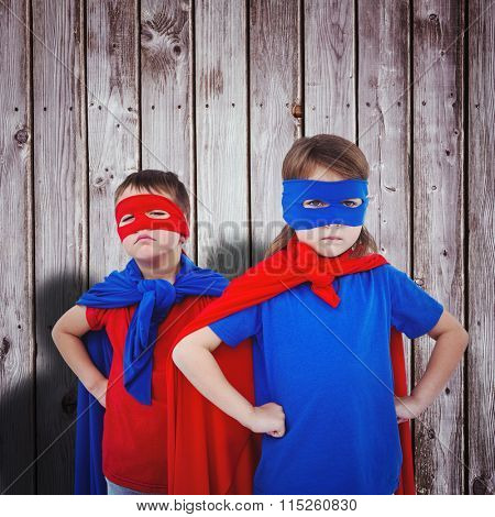 Masked kids pretending to be superheroes against digitally generated grey wooden planks