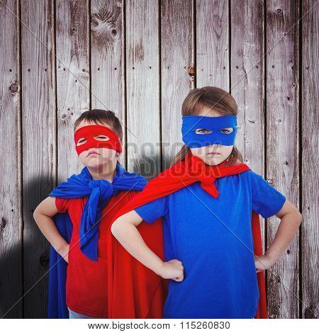Masked kids pretending to be superheroes against digitally generated grey wooden planks