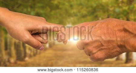 Cropped hands of people holding fingers against walkway along lined trees in the park