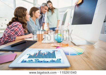 Blue data against tablet in the foreground with business people in the background