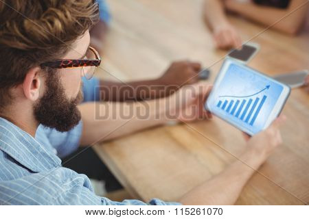 Blue data against high angle view of man holding digital tablet