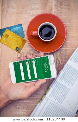 Credit Card against overhead view of person using smart phone by coffee