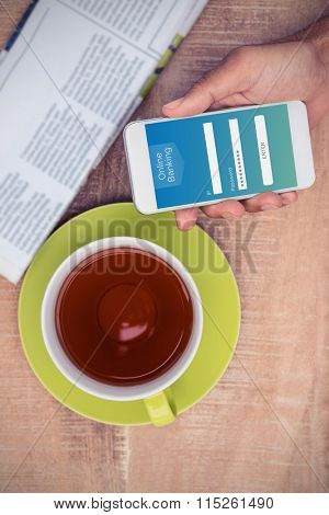 Online banking against cropped image of man holding smart phone