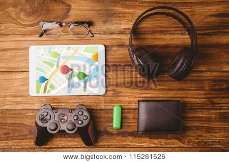 Multi colored navigation pointers on map against tablet and glasses next to joystick music headphone and wallet