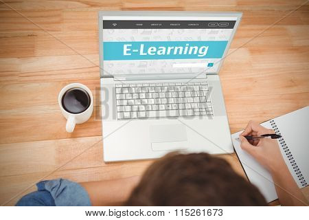 E-learning interface against hipster writing on spiral notebook by laptop at desk in office