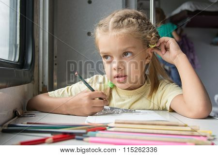 Six Year Old Girl Lost In Thought Looked Out The Window Drawing Pencils In Second-class Train Carria