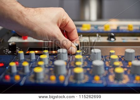 Hand Of Audio Engineer Turning The Knobs On An Audio Mixer