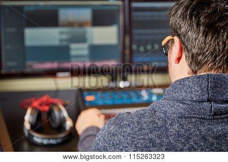 Audio Engineer Sitting In Front Of A Mixing Desk