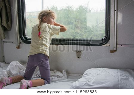 Four-year Girl On The Side Of The Shelf Of The Train Looking Out The Window