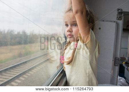 Four-year Girl With Astonishment Looks In The Window Of A Train