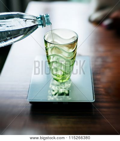 Pouring Water In Glas On Electronic Scale