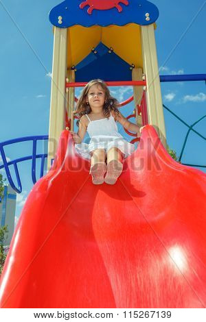 Curly preschool girl sitting on the top of a kids slide, at the playground
