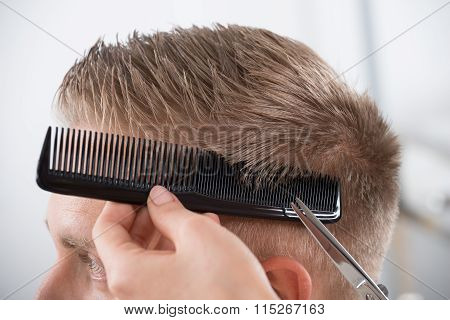 Man Getting Haircut From Hairdresser At Salon