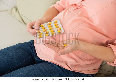 Pregnant Woman Taking Vitamin Pill At Home