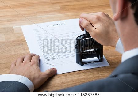 Businessman Stamping Contract Document At Desk
