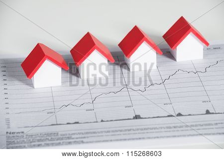 House Models On Financial Chart At Desk