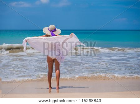 woman in white sarong blowing on the beach