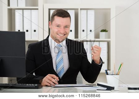 Happy Businessman Clenching Fist At Desk In Office