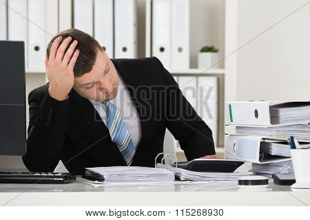 Tensed Accountant Sitting At Desk In Office