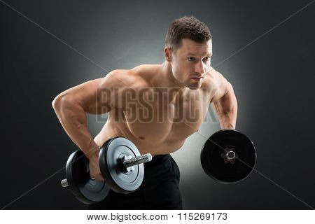 Determined Muscular Man Lifting Dumbbells