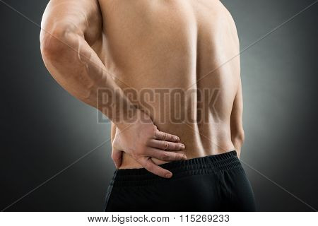 Midsection Of Muscular Man Suffering From Backache