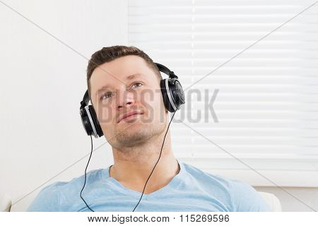 Thoughtful Man Listening Music Through Headphones