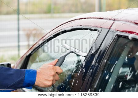 Serviceman Cleaning Car Window At Service Station