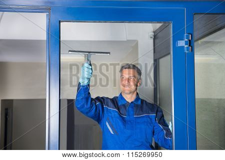 Male Worker Cleaning Glass With Squeegee