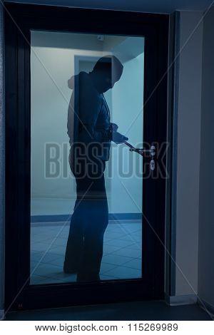 Burglar Using Crowbar To Open Glass Door