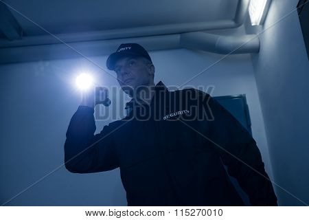 Security Guard Searching With Flashlight In Office