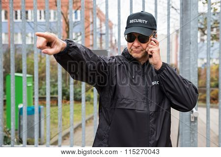 Security Guard Gesturing While Using Walkie-talkie