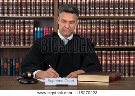 Judge Writing On Paper At Table In Courtroom
