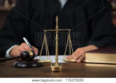 Law Scales On Table With Judge Writing In Background