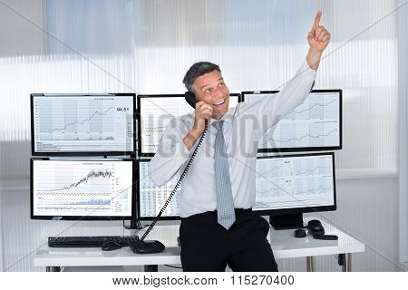 Happy Stock Trader Pointing Upwards While Using Telephone