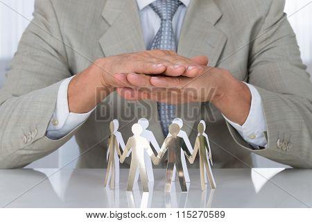 Businessman Protecting Paper Team On Desk