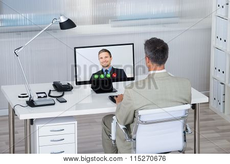 Businessman Videoconferencing With Partner On Computer At Desk